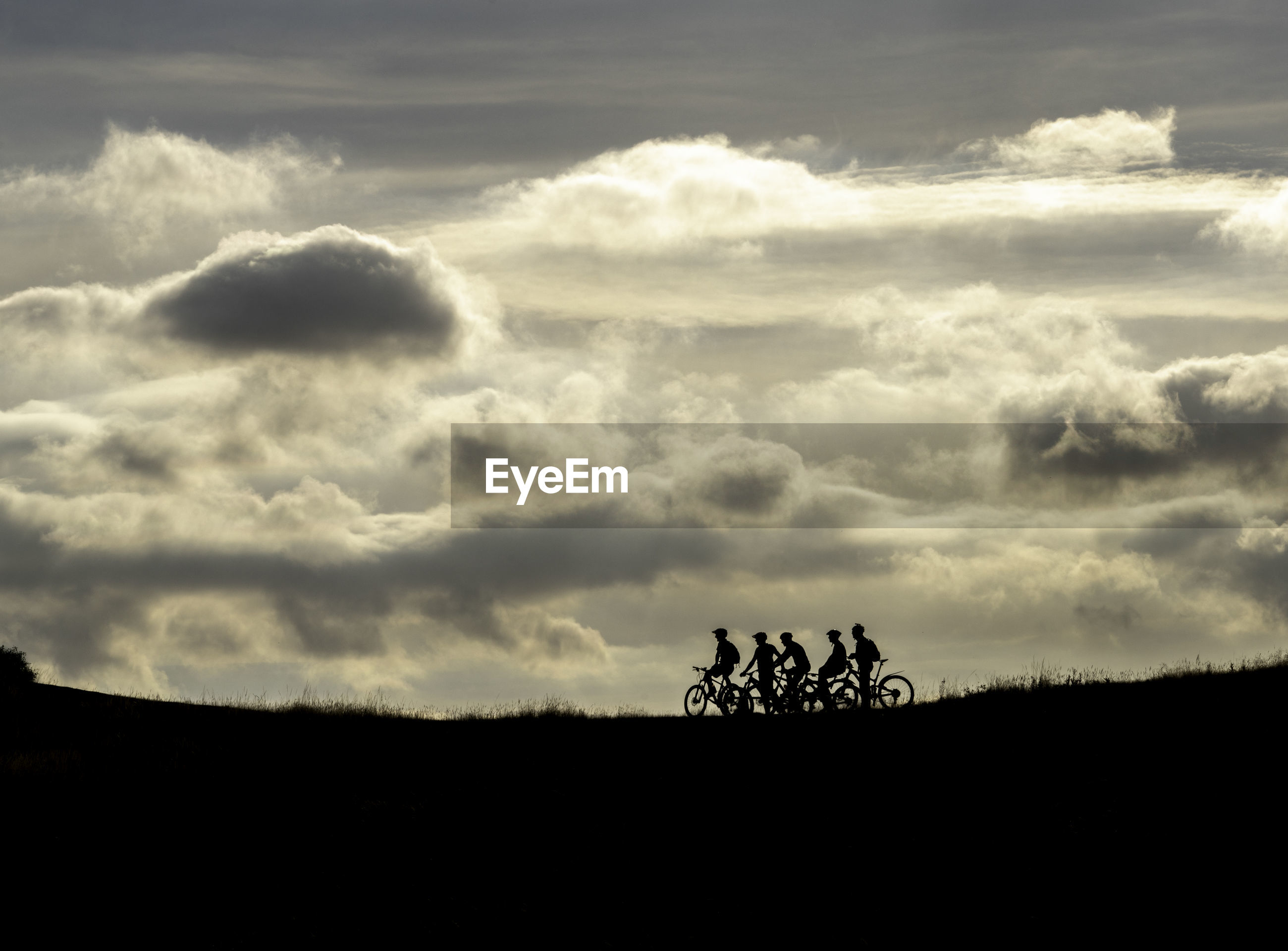 Silhouette people riding bicycles on field against cloudy sky during sunset