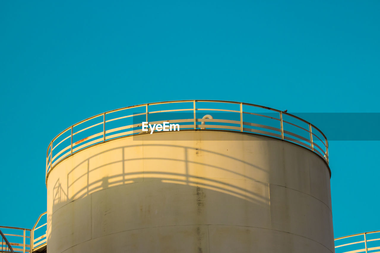 copy space, fuel and power generation, low angle view, industry, storage tank, sky, architecture, clear sky, blue, nature, no people, container, silo, factory, fuel storage tank, built structure, storage compartment, metal, day, oil industry, outdoors