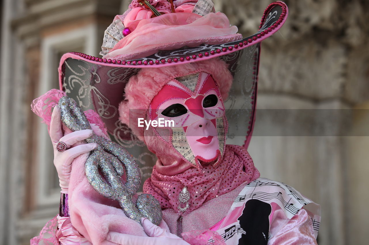 costume, celebration, tradition, cultures, mask - disguise, real people, focus on foreground, pink color, traditional festival, leisure activity, arts culture and entertainment, day, outdoors, one person, built structure, lifestyles, performance, traditional dancing, stage costume, men, architecture, close-up, clown, chinese dragon