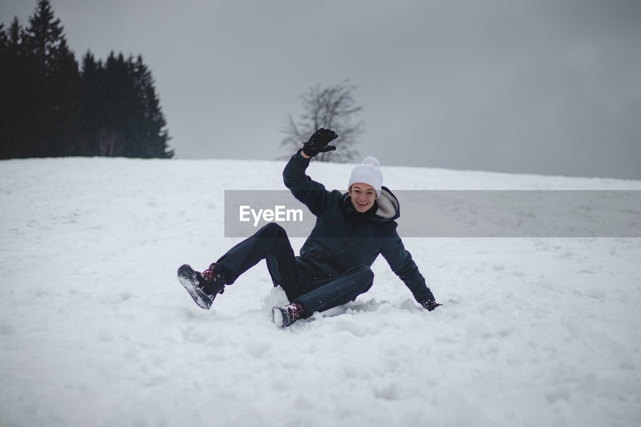 Teenager falls from a plastic snowboard and falls hard on the snow and sprawls. inventing nonsense