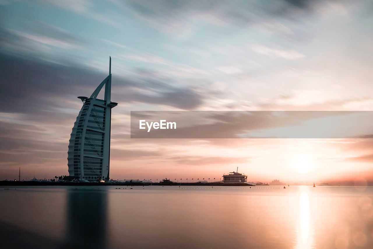sunset, water, sky, cloud - sky, reflection, no people, sea, nature, outdoors, architecture, beauty in nature, windmill, day