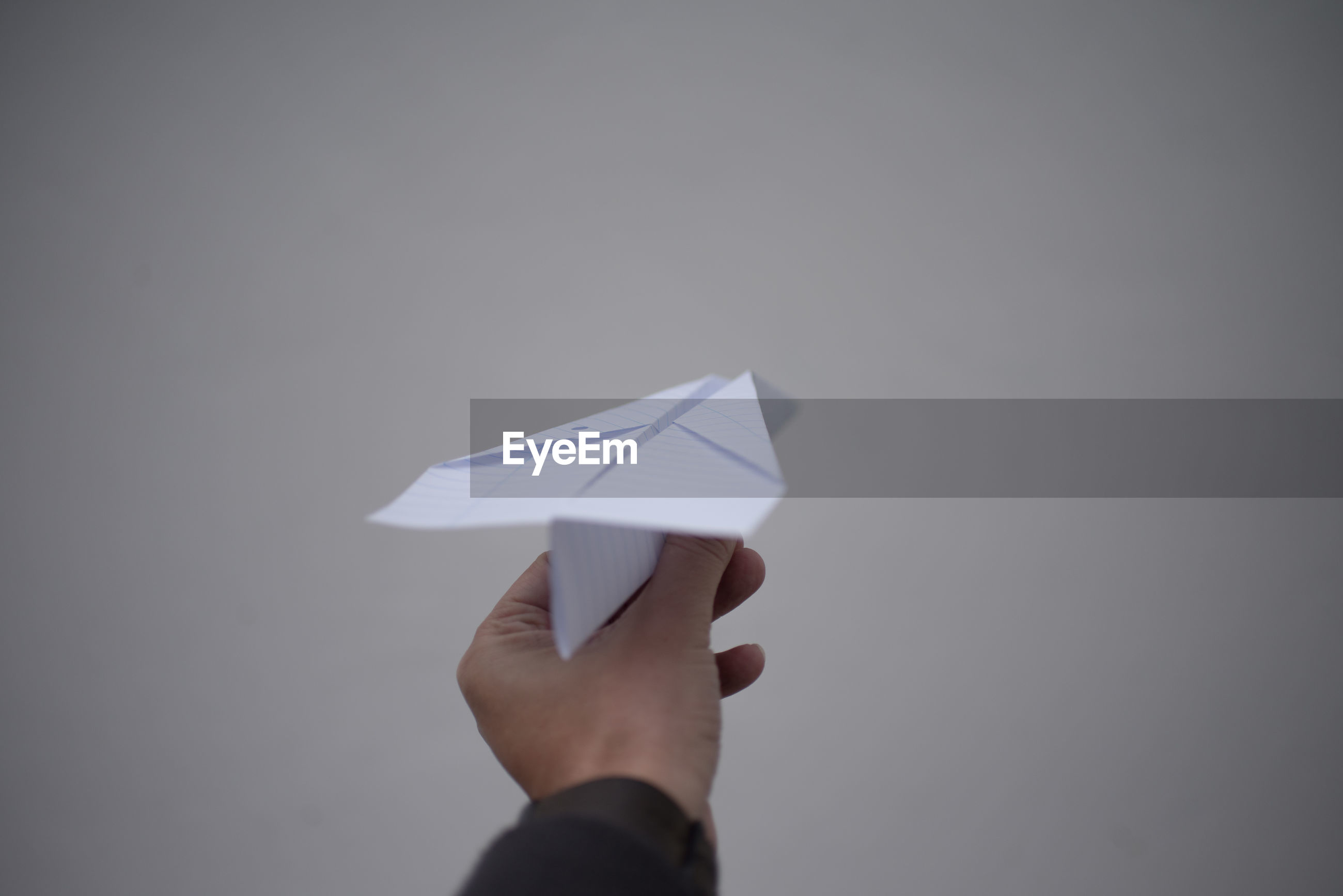 Cropped hand holding paper airplane against gray background