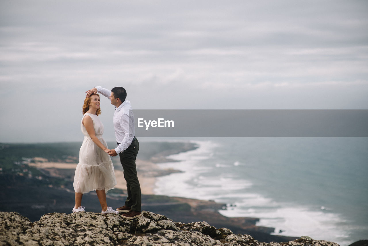 Romantic Couple Standing On Cliff By Sea Against Sky
