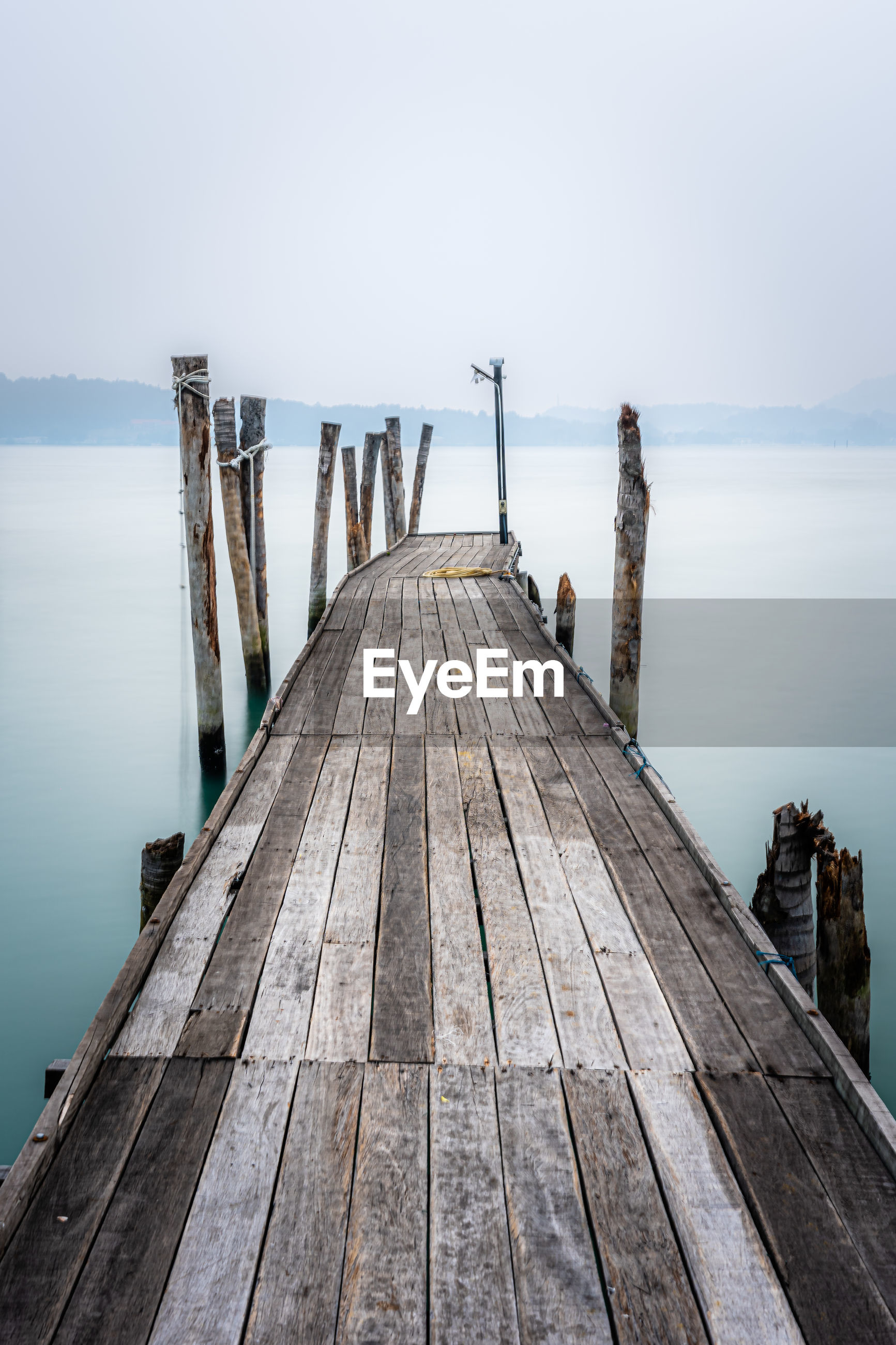 WOODEN JETTY ON PIER AGAINST SKY