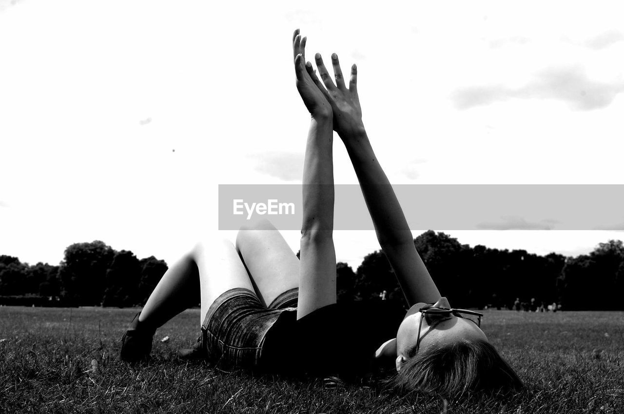 real people, lying down, field, one person, young adult, young women, full length, leisure activity, sky, lying on back, grass, day, relaxation, outdoors, lifestyles, women, tree, beautiful woman, nature, people