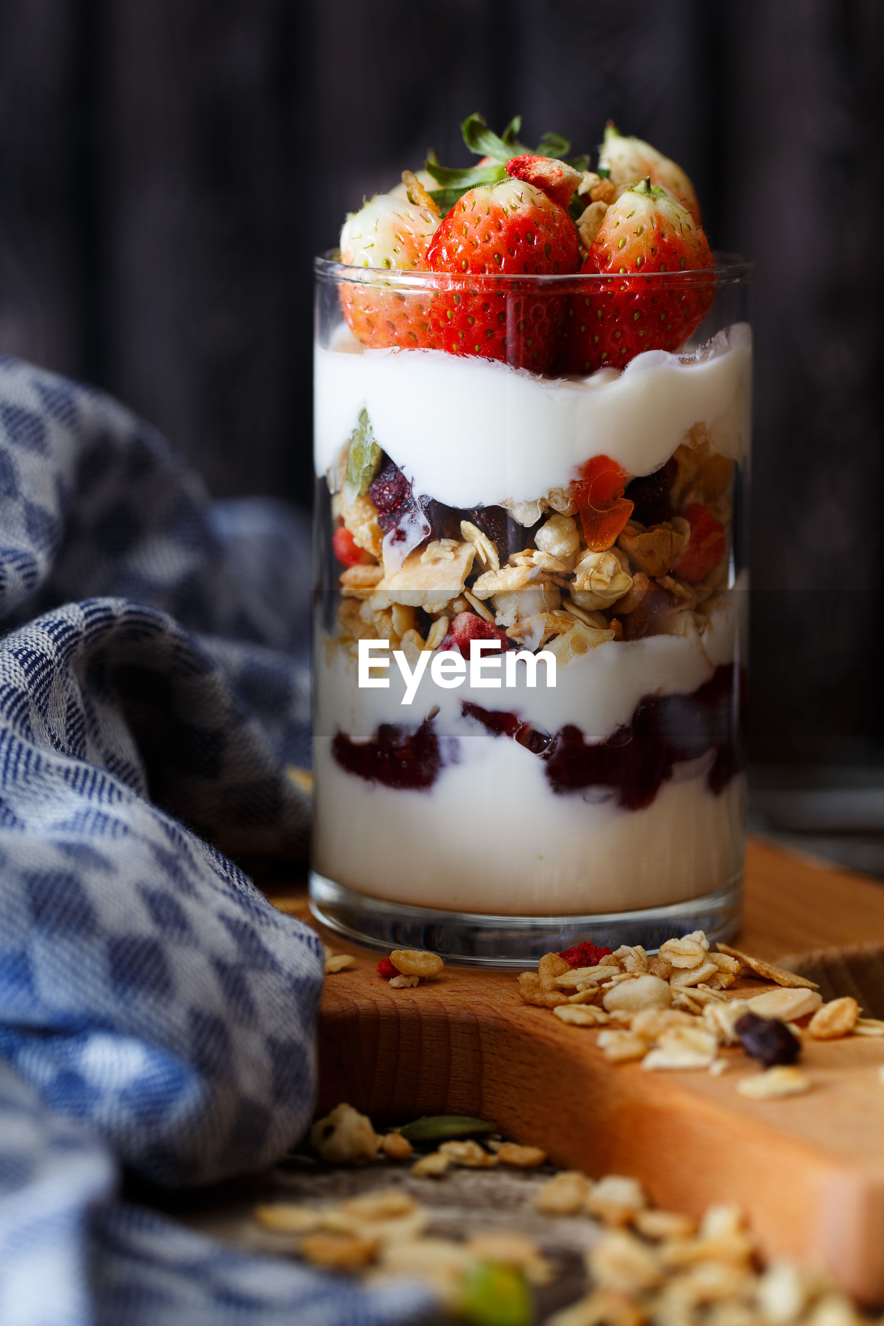 Close-up of strawberries with yogurt and granola in glass on table
