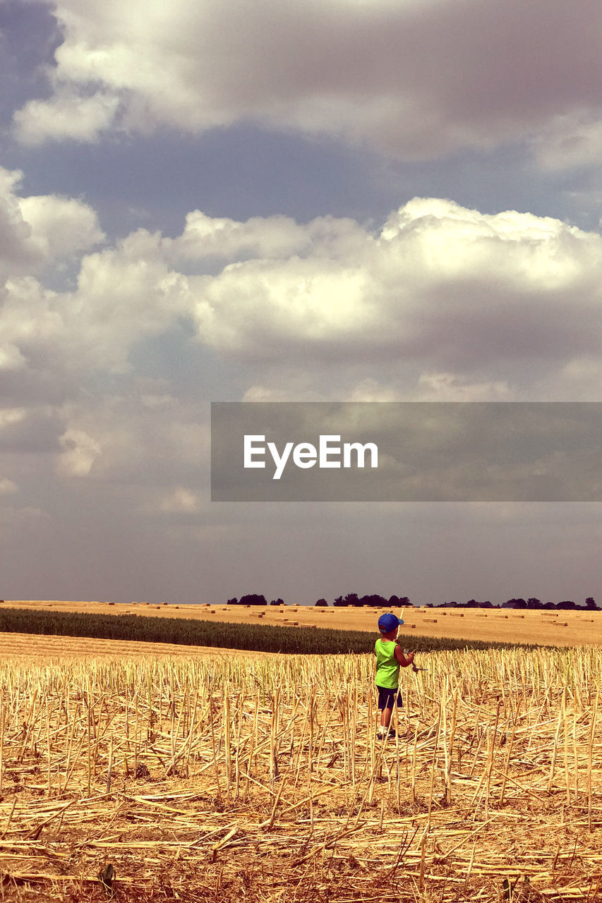 cloud - sky, sky, field, land, agriculture, landscape, environment, one person, rural scene, real people, nature, farm, day, beauty in nature, rear view, scenics - nature, men, plant, tranquility, outdoors