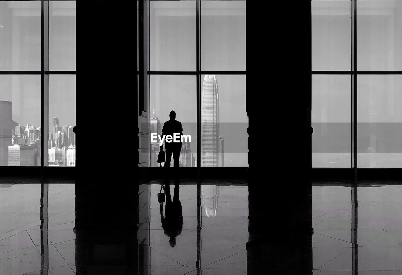 Silhouette Man Looking At International Finance Centre Through Window