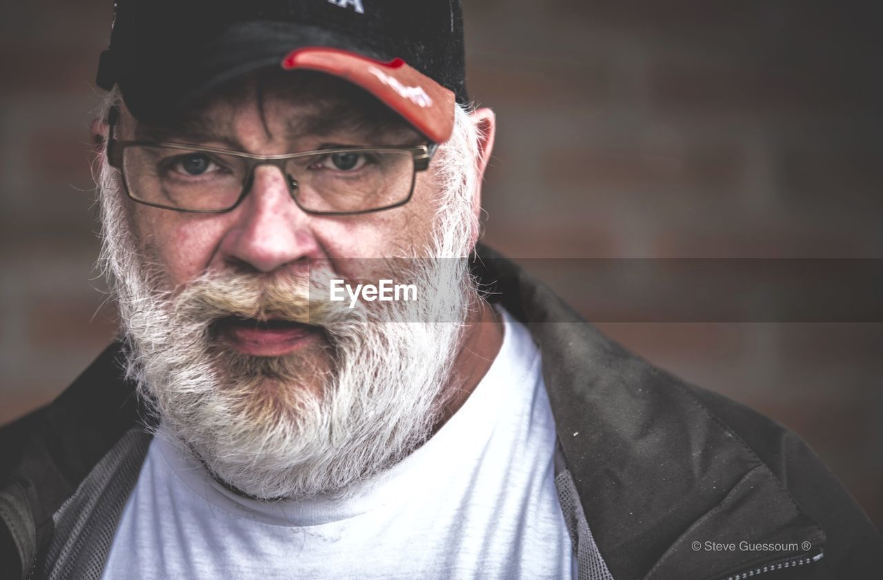real people, looking at camera, senior adult, portrait, beard, one person, senior men, lifestyles, front view, eyeglasses, leisure activity, headshot, happiness, outdoors, day, close-up
