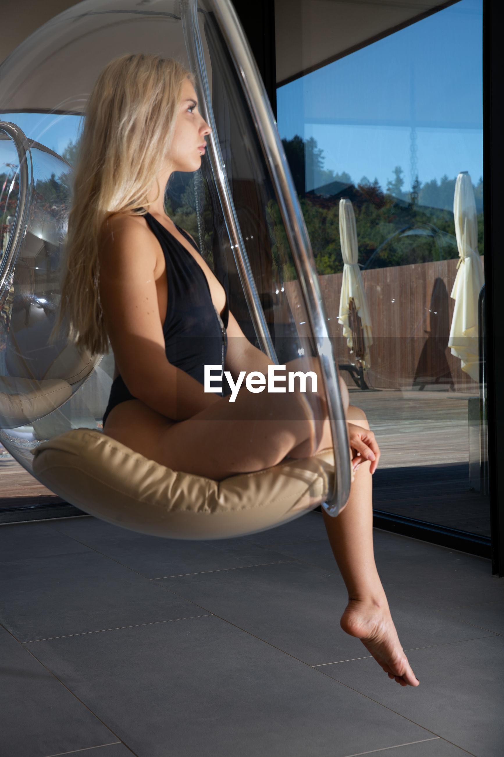 WOMAN SITTING IN GLASS WINDOW OF BUS