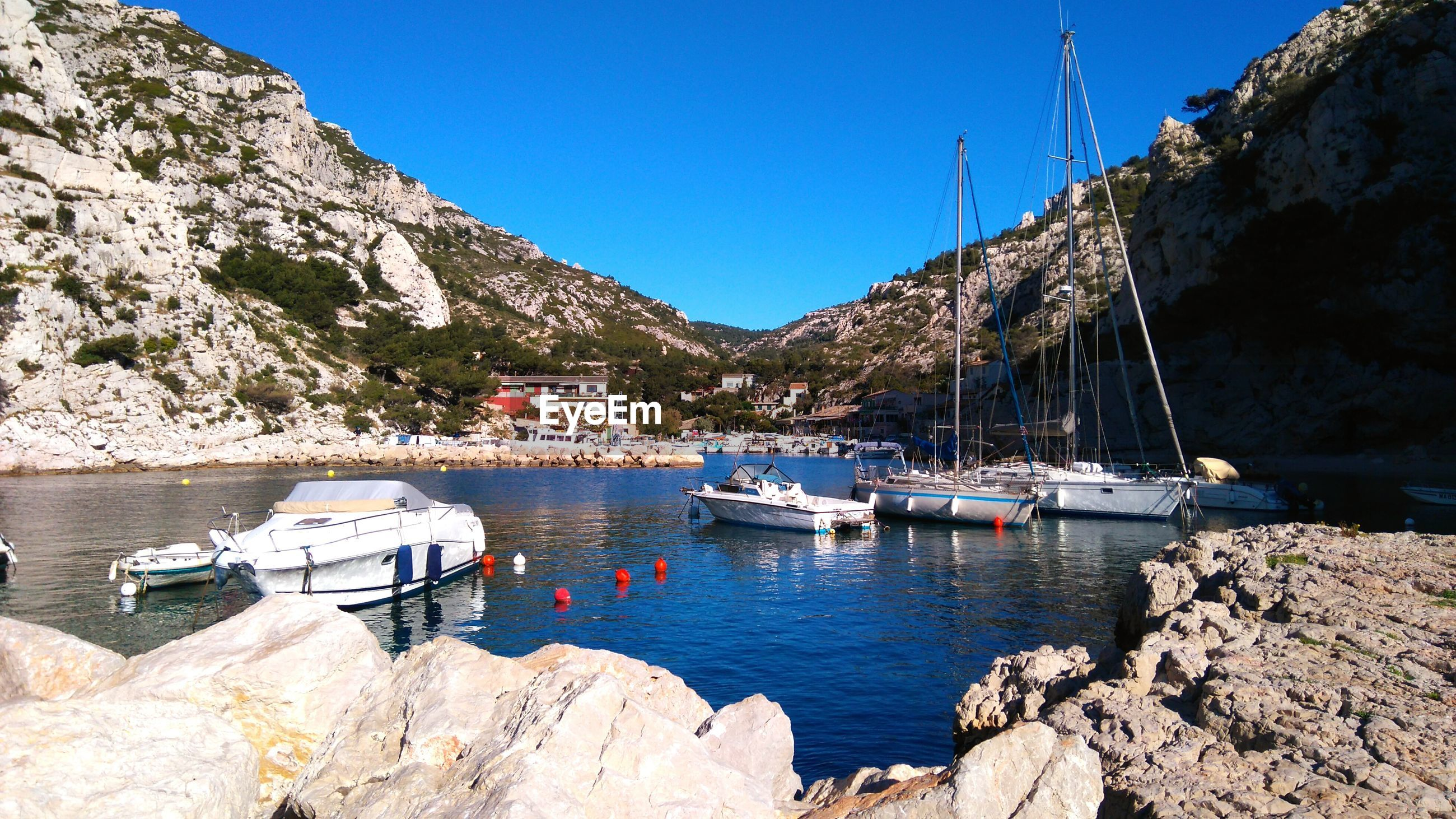 nautical vessel, mode of transport, boat, transportation, water, mountain, sunlight, rock - object, moored, clear sky, nature, day, sunny, no people, waterfront, sea, outdoors, mast, tranquil scene, sailboat, blue, yacht, beauty in nature, scenics, architecture, travel destinations, built structure, building exterior, harbor, sailing, tree, sky