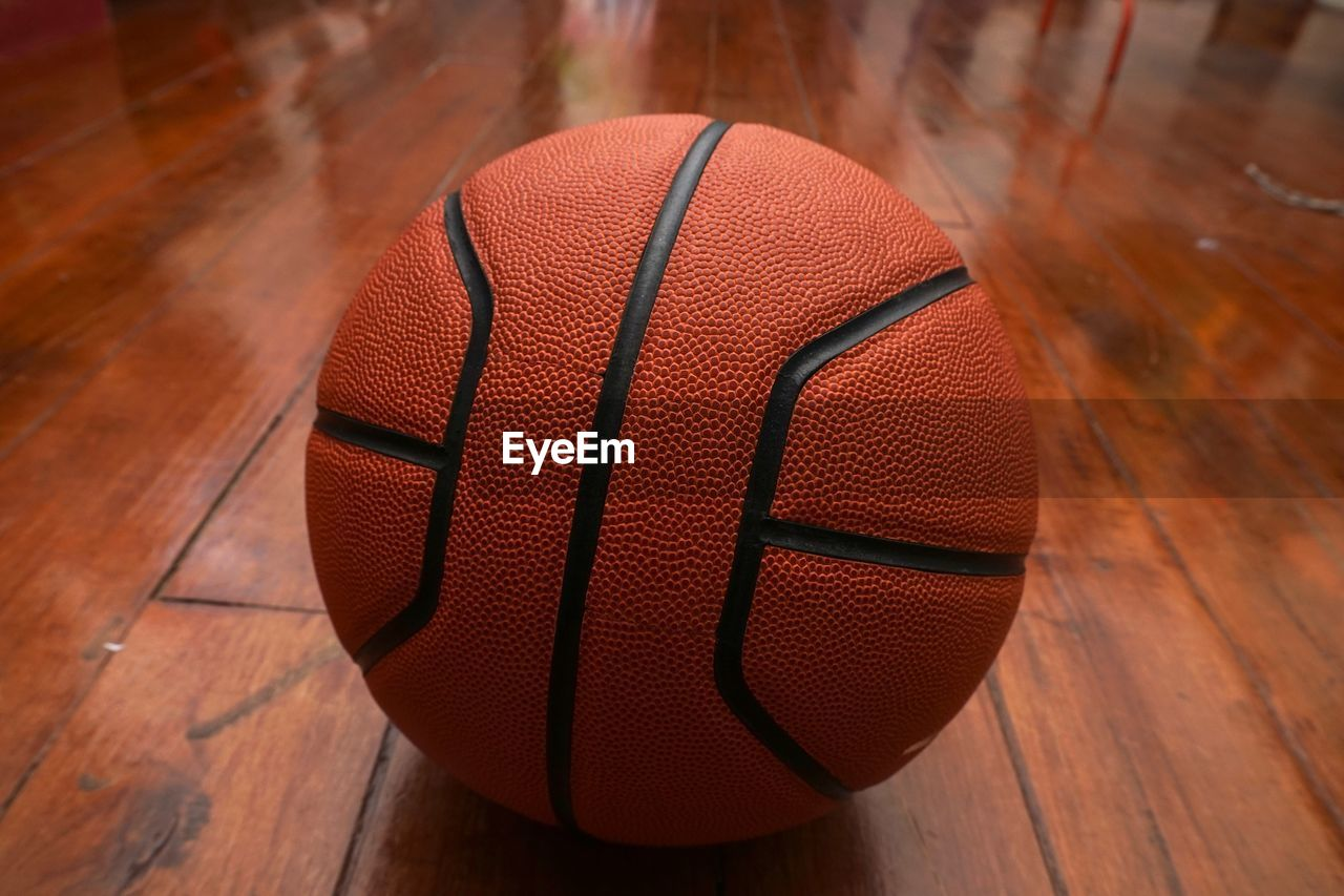basketball - sport, ball, sport, hardwood floor, wood - material, wood, basketball - ball, indoors, close-up, flooring, sphere, orange color, court, textured, no people, still life, single object, brown, floorboard, focus on foreground, leather