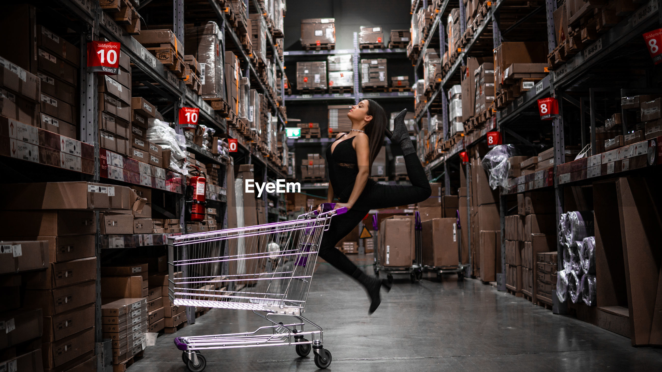Side view of woman dancing with shopping cart on floor in warehouse
