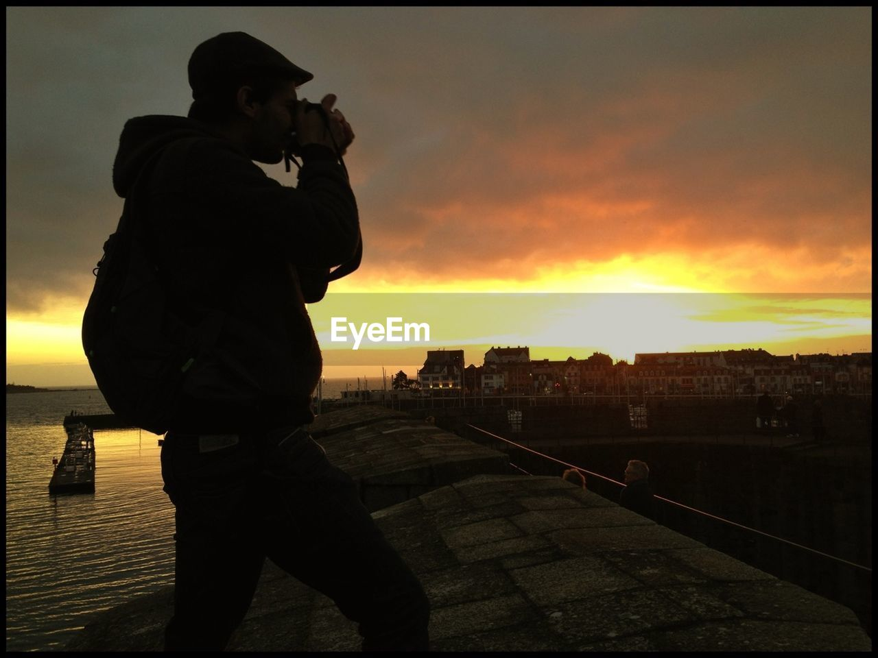 Man Photographing Against Cloudy Sky During Sunset