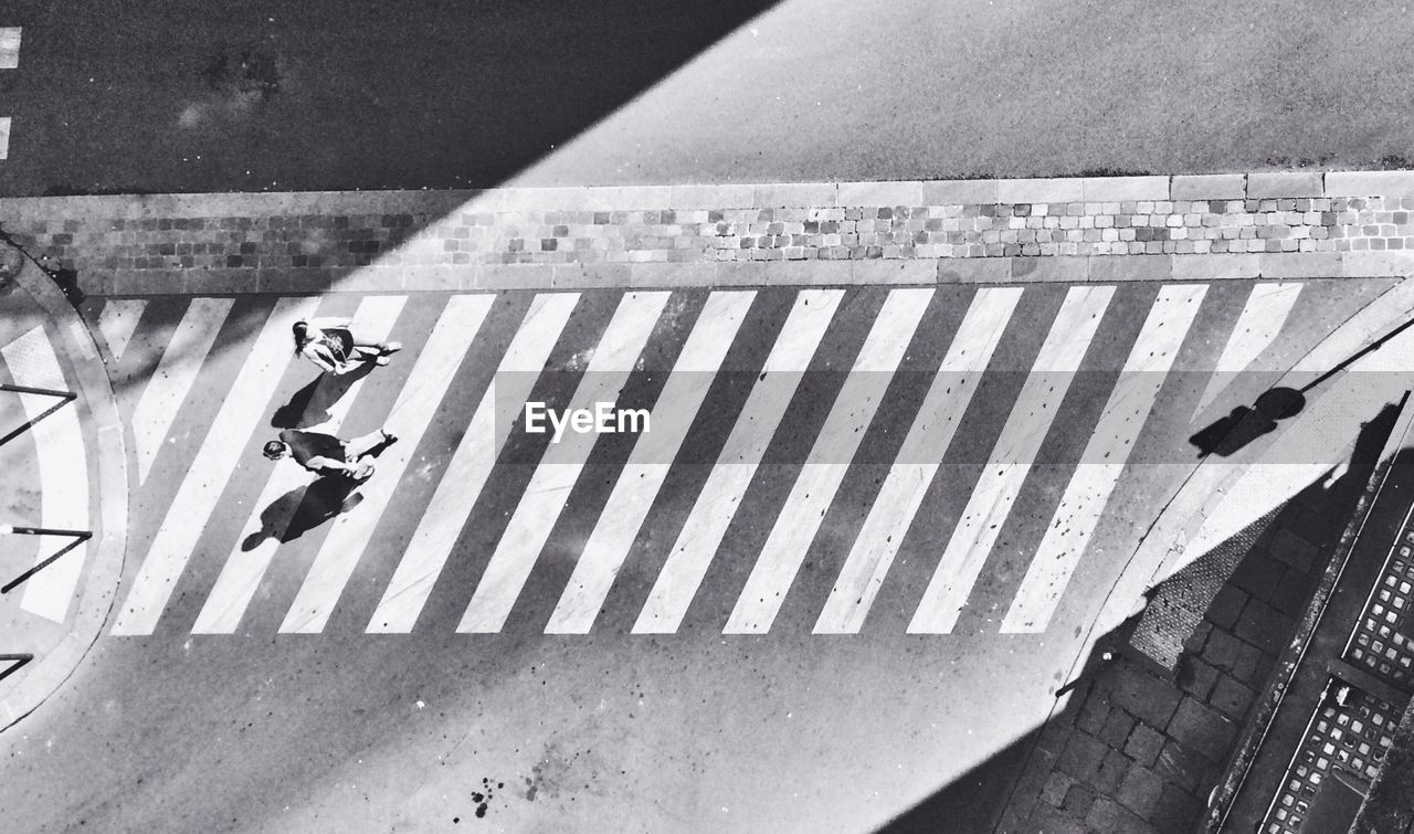 High angle view of man and woman walking on zebra crossing during sunny day