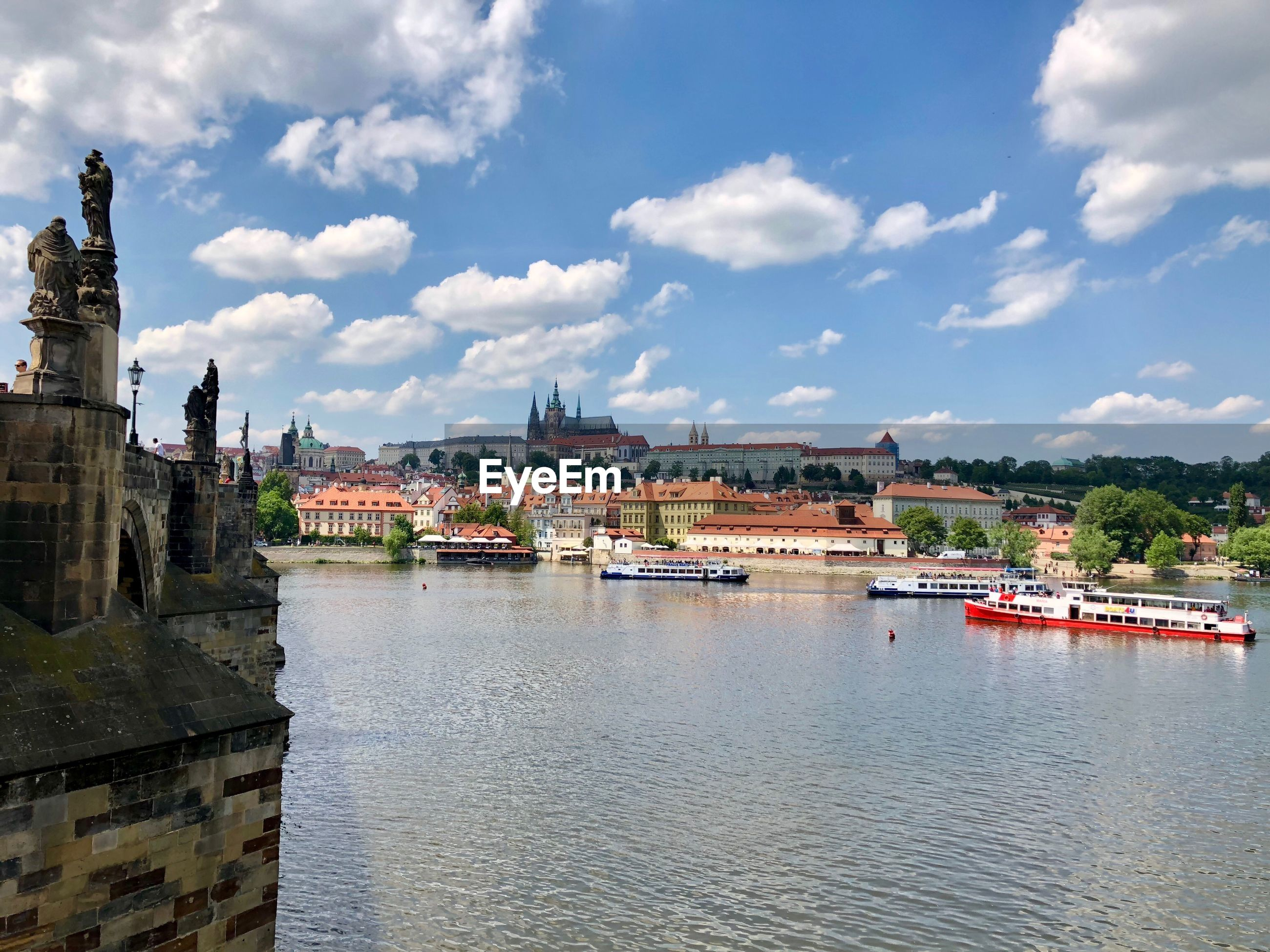 VIEW OF BUILDINGS BY RIVER AGAINST SKY