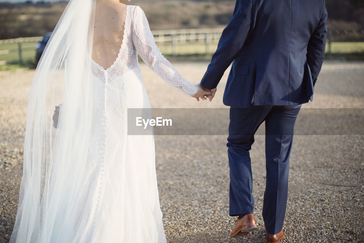 Low section of bride and bridegroom holding hands while walking on field