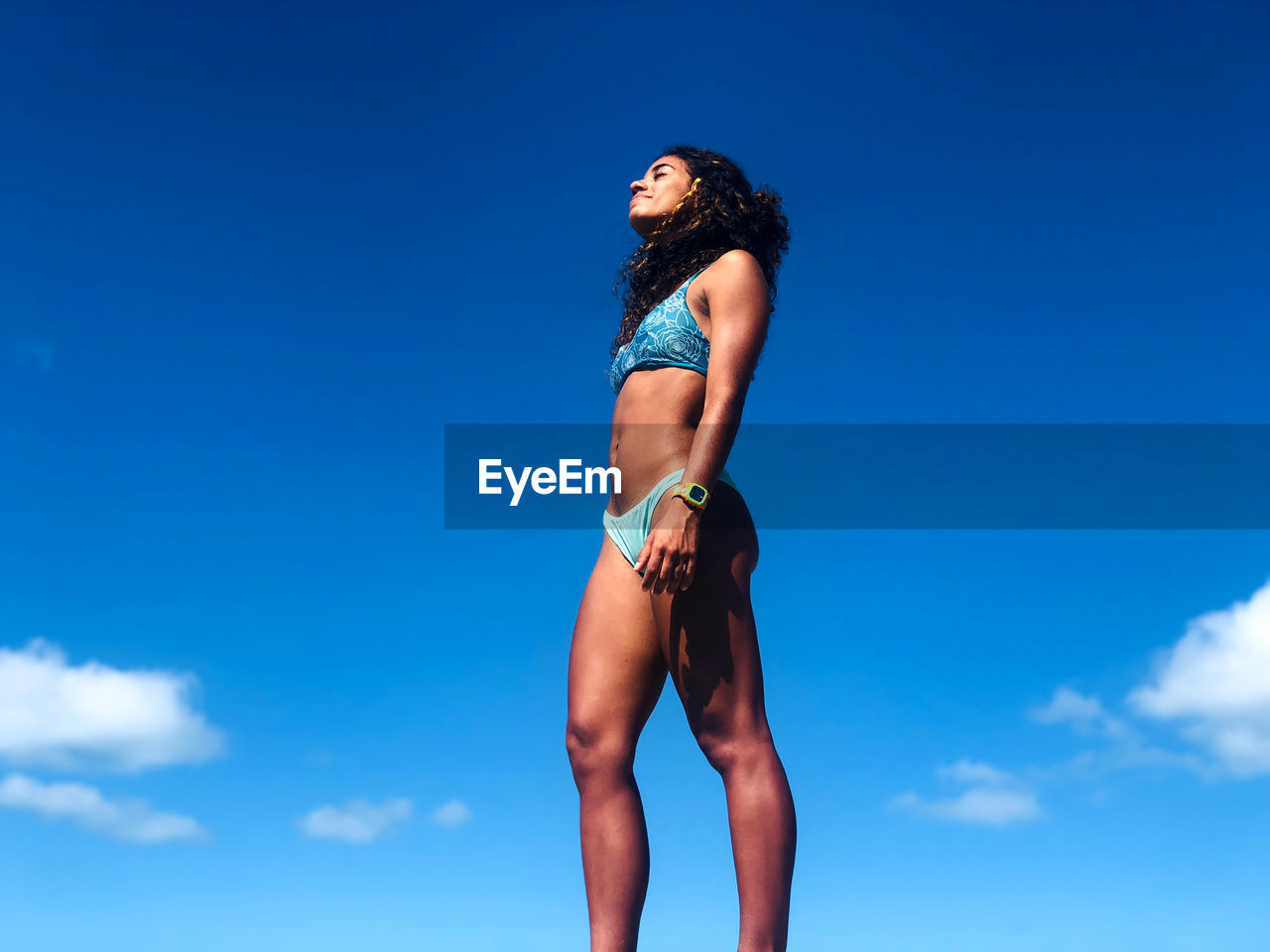 Low angle view of woman in bikini standing against blue sky