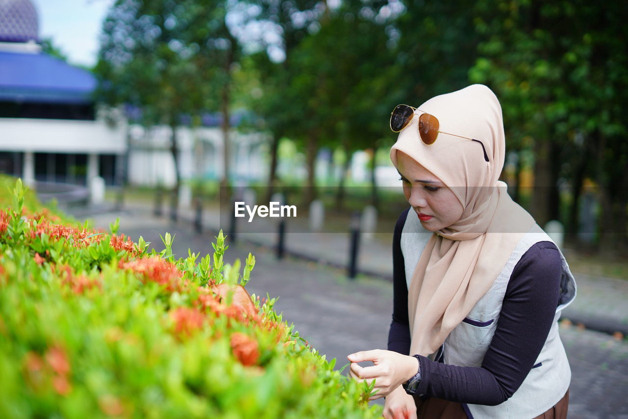 Young woman wearing hijab touching plant at park