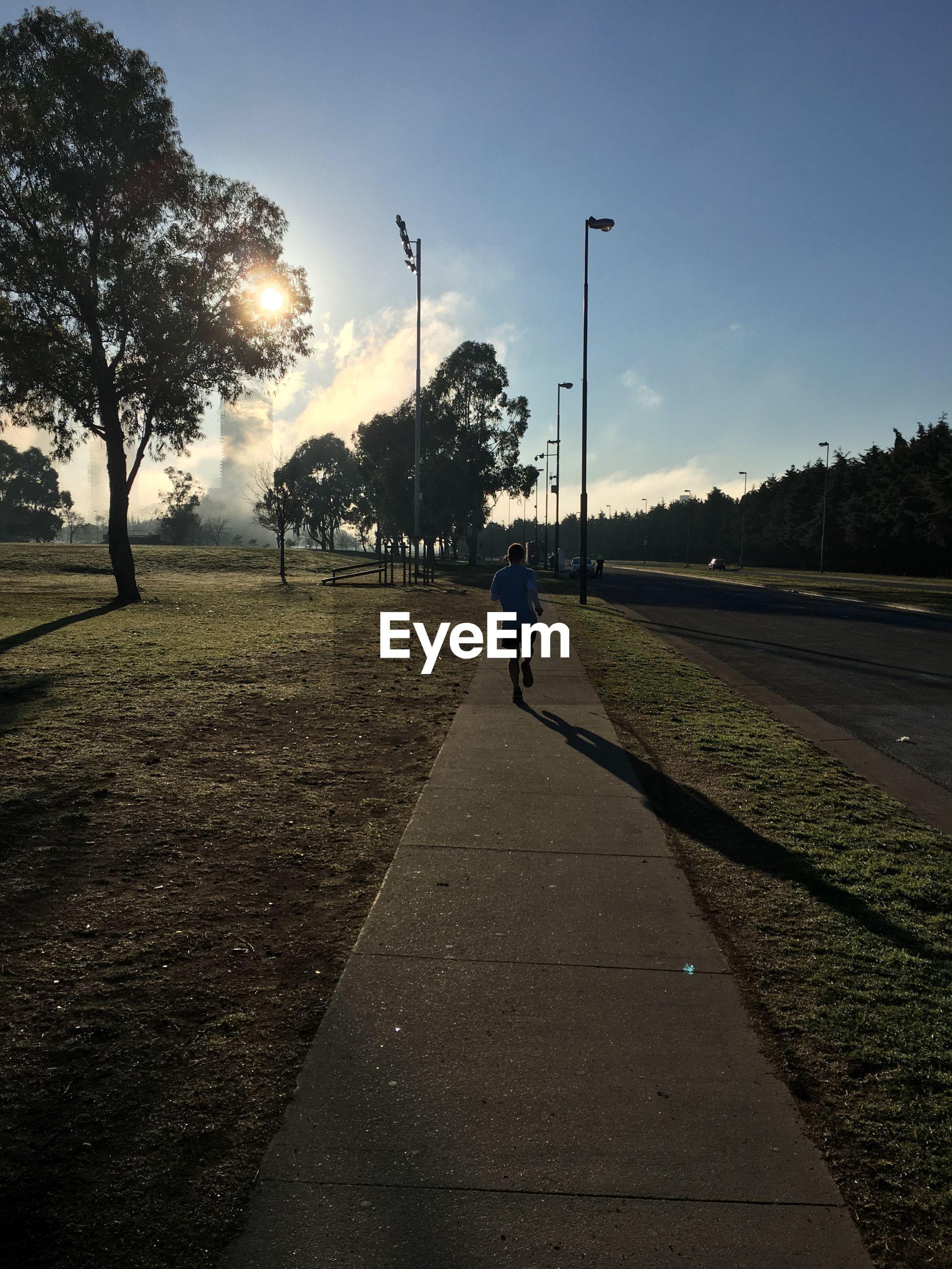 Rear view of man walking on footpath against sky