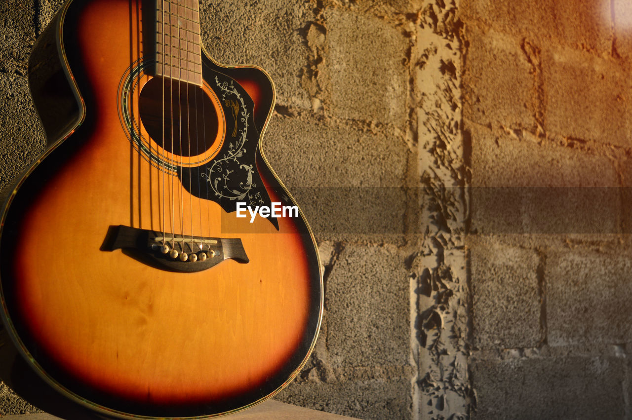 string instrument, musical instrument, wall - building feature, guitar, music, string, musical instrument string, musical equipment, no people, wall, arts culture and entertainment, indoors, still life, close-up, built structure, brown, day, acoustic guitar, architecture, craft