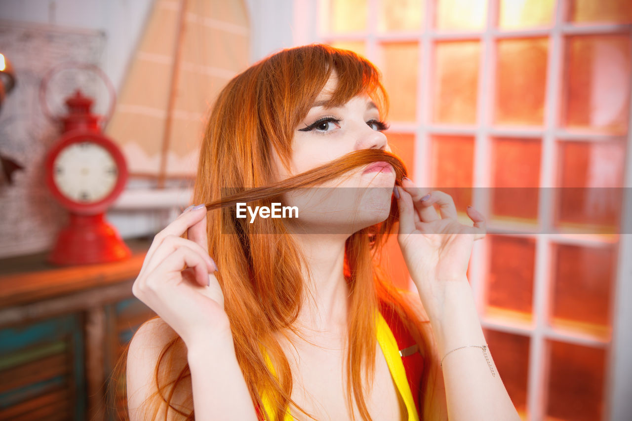 Portrait Of Beautiful Redhead Woman Making Mustache With Hair In Room