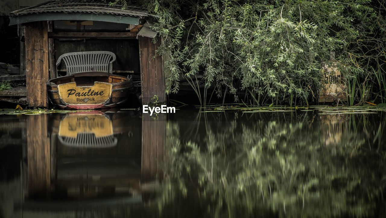 Abandoned boat in boathouse with reflection in lake