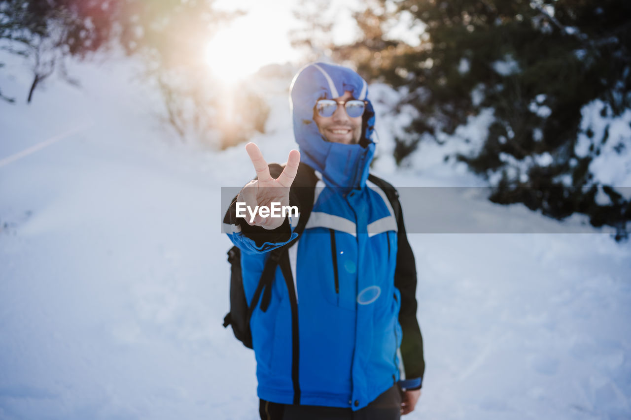 Portrait of man gesturing while standing on snow covered land during winter