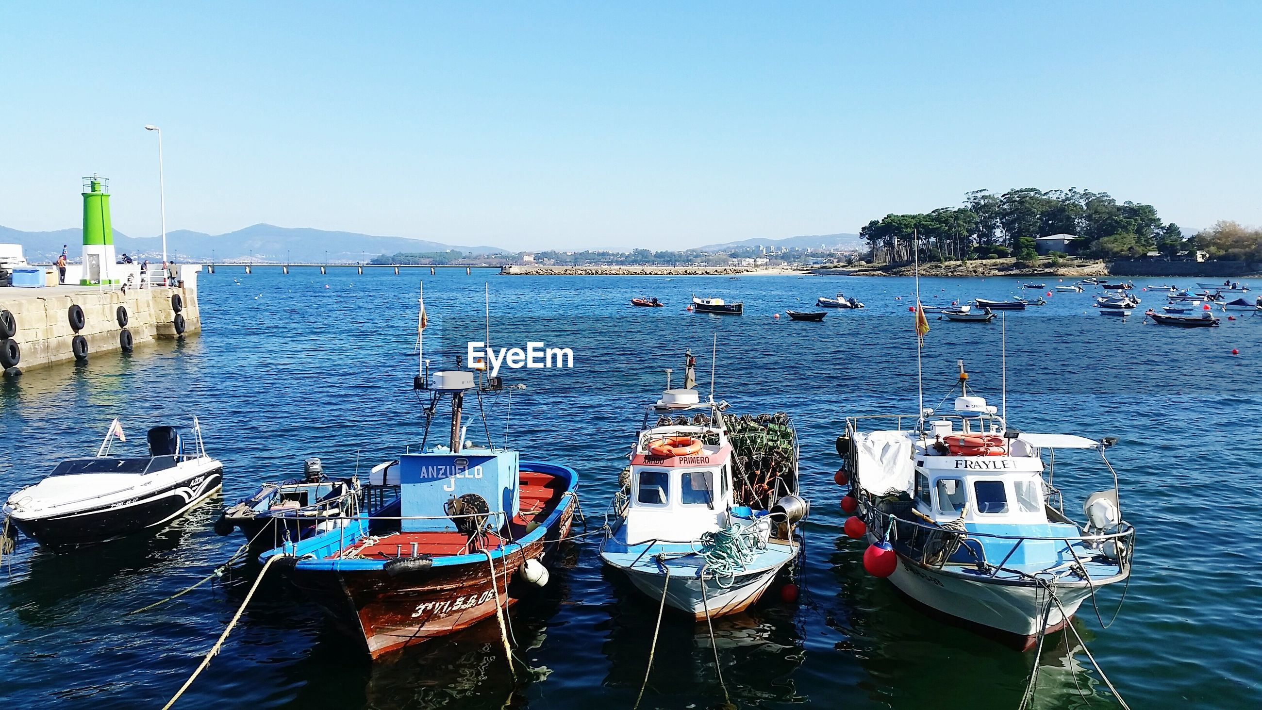 BOATS MOORED ON SEA AGAINST CLEAR BLUE SKY