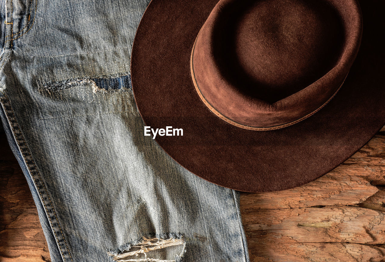 Directly above shot of jeans and cowboy hat on wooden table
