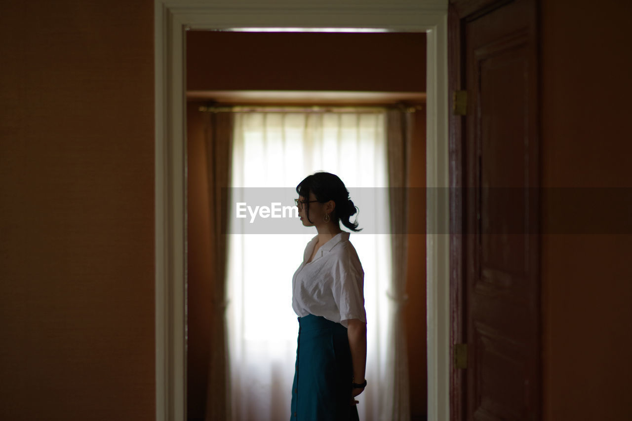 Side view of thoughtful young woman standing at home