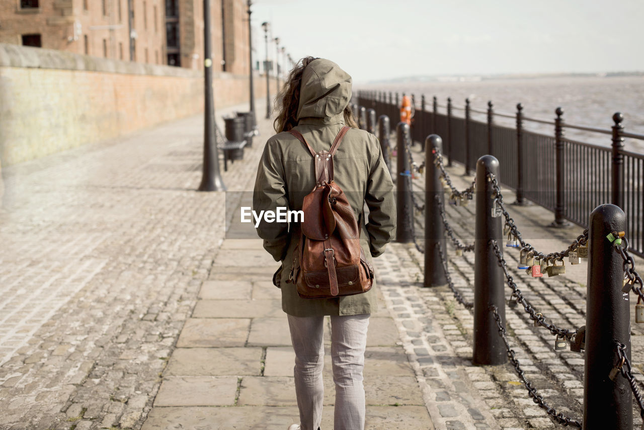 Rear View Of Woman Carrying Backpack While Walking On Sidewalk By Sea