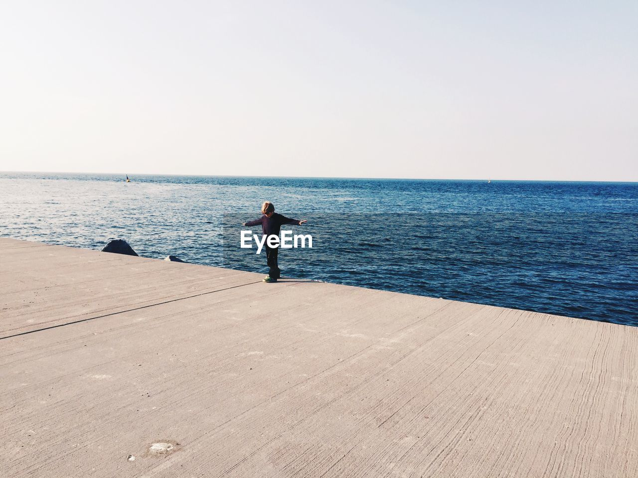 View Of Person Standing With Arms Out By The Sea