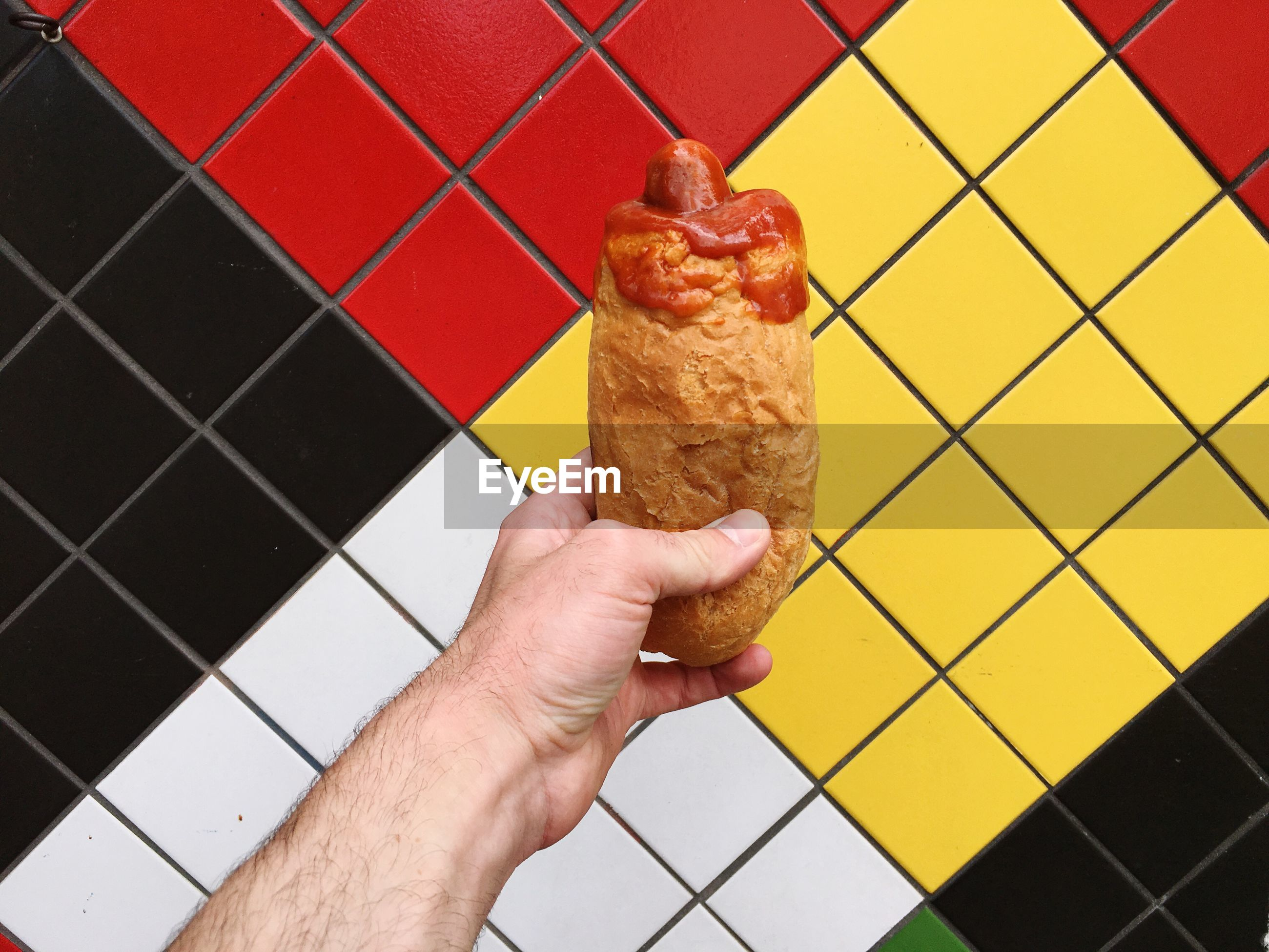 Cropped hand holding bread roll in front of tiled wall