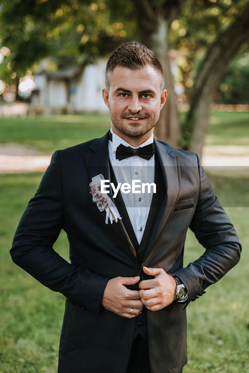 Portrait of groom standing at park