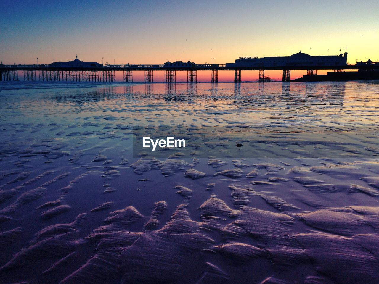 Silhouette of brighton pier over sea at dusk