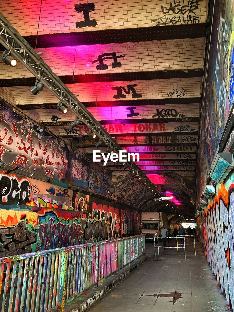 multi colored, architecture, graffiti, indoors, creativity, built structure, text, no people, lighting equipment, art and craft, ceiling, illuminated, direction, wall - building feature, street art, wall, in a row, the way forward, building, communication