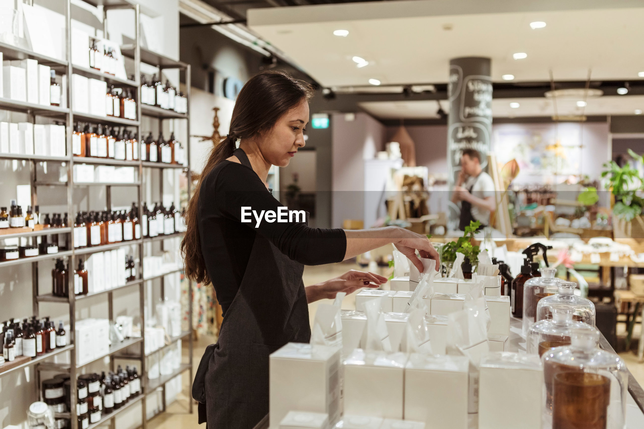 SIDE VIEW OF YOUNG WOMAN STANDING BY STORE