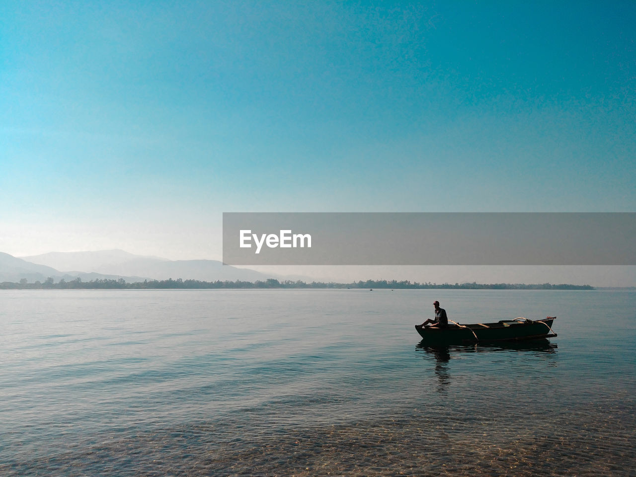 Man In Boat Sailing On Sea Against Clear Sky