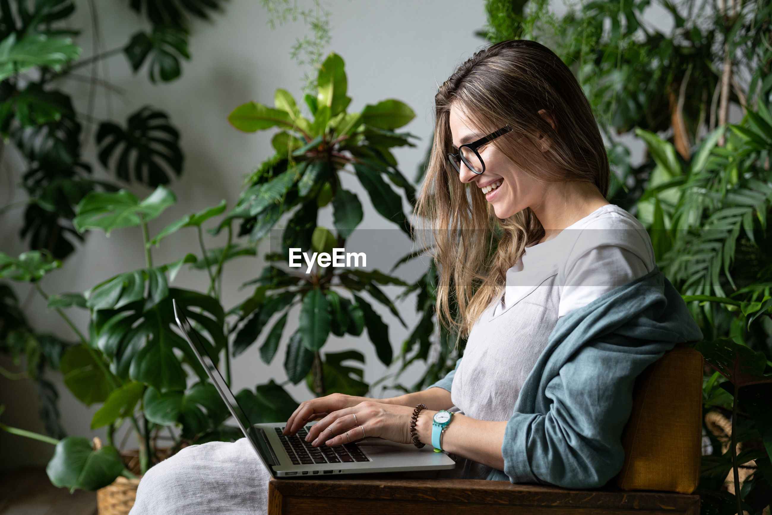 Young woman using laptop by plants