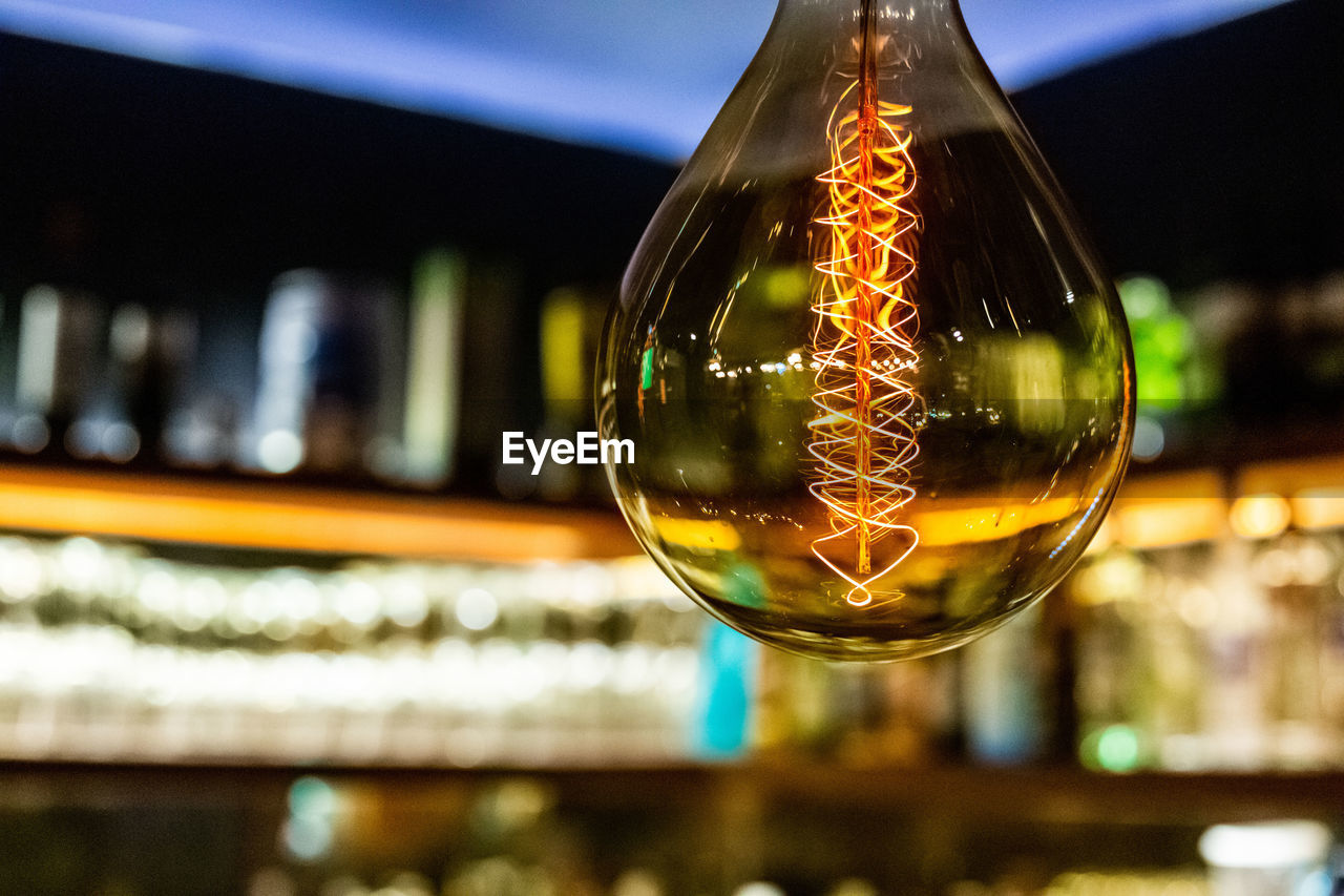 focus on foreground, transparent, glass - material, close-up, no people, illuminated, reflection, fragility, glass, indoors, vulnerability, selective focus, sphere, bubble, shiny, lighting equipment, light bulb, filament, shape