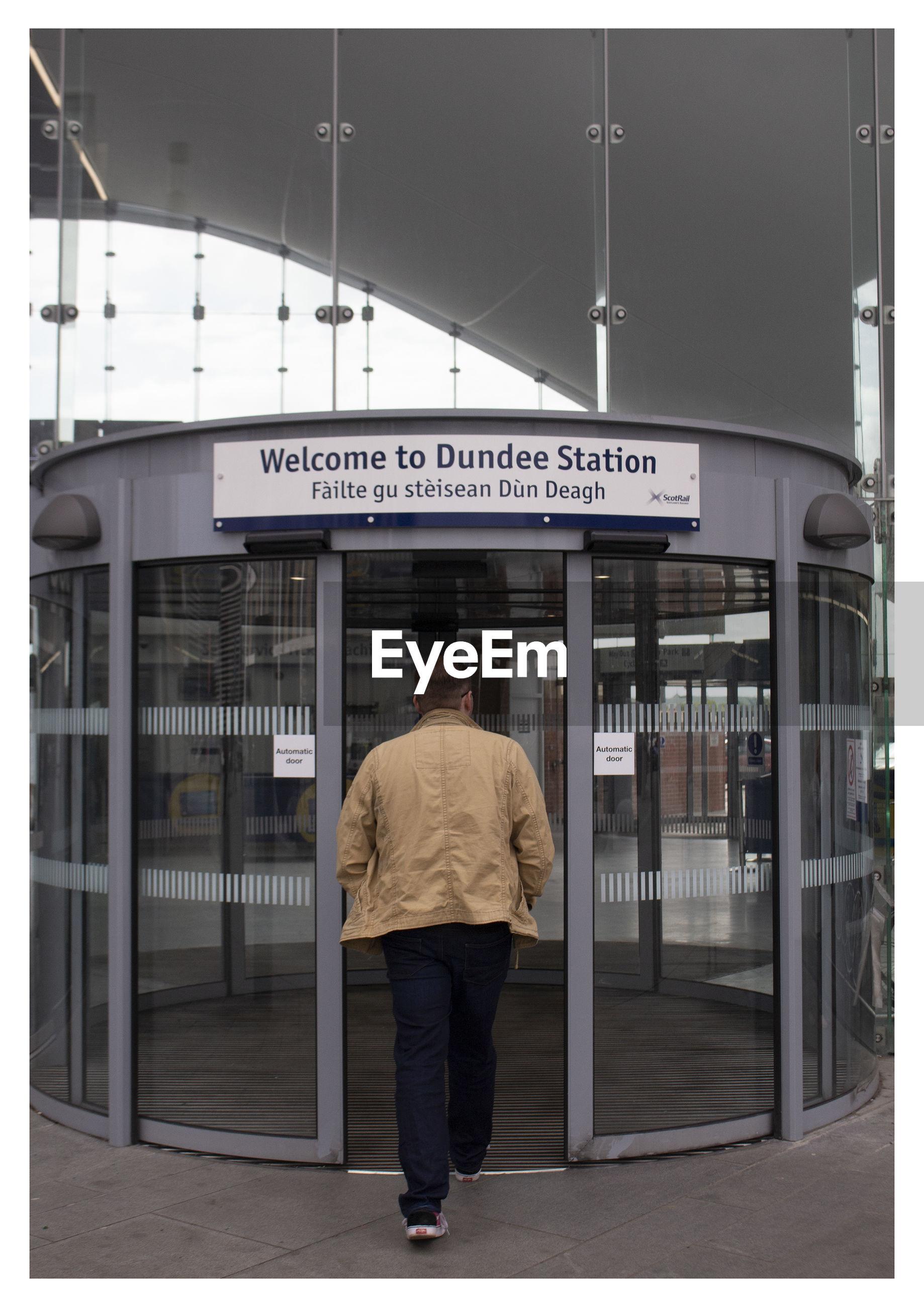 REAR VIEW OF MAN WALKING ON BUS