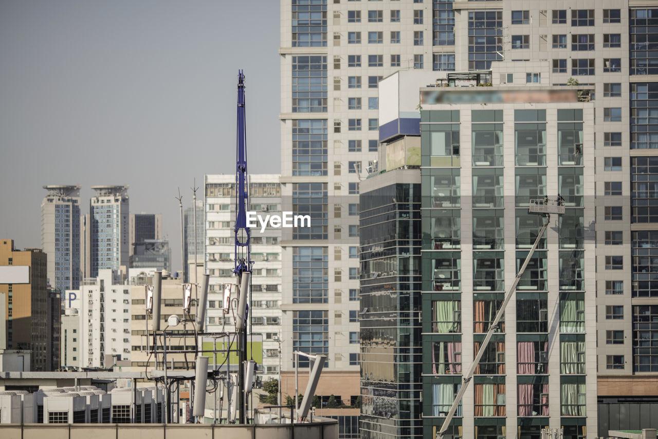 Crane By Buildings In City