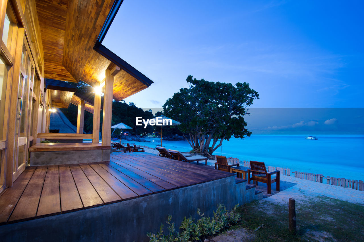 water, sky, nature, architecture, sea, swimming pool, beauty in nature, scenics - nature, tranquil scene, no people, tree, dusk, built structure, pool, tranquility, wood - material, illuminated, blue, building exterior, outdoors, luxury