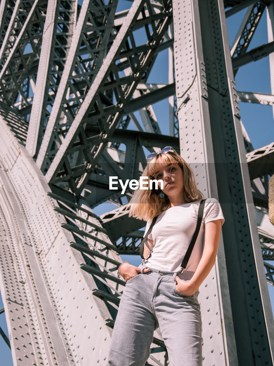 Low angle portrait of woman standing on bridge