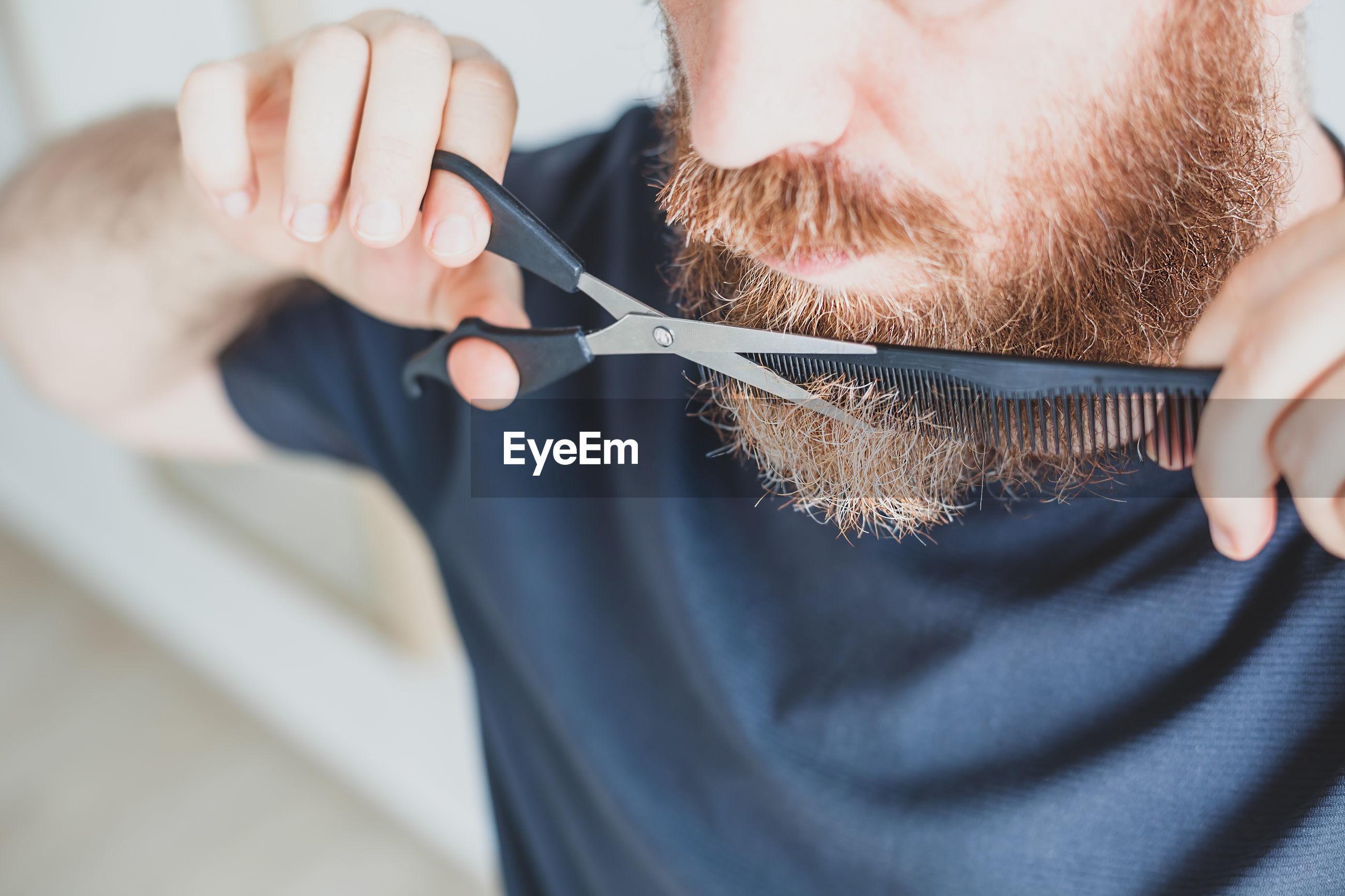 Close-up of man cutting beard