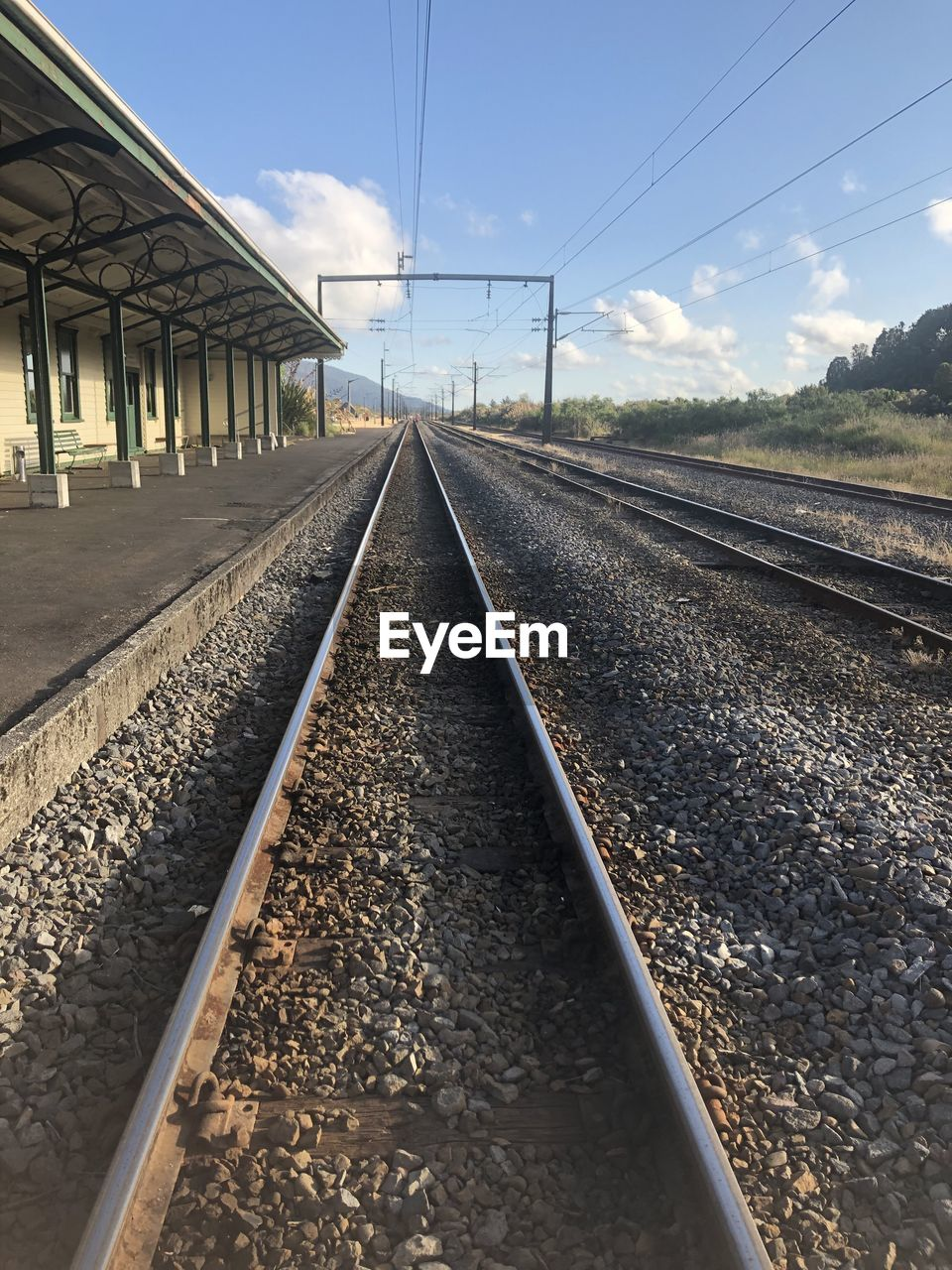 rail transportation, track, railroad track, transportation, sky, the way forward, nature, diminishing perspective, direction, no people, vanishing point, gravel, day, sunlight, connection, cable, cloud - sky, built structure, public transportation, electricity, outdoors, surface level, long, power supply, parallel