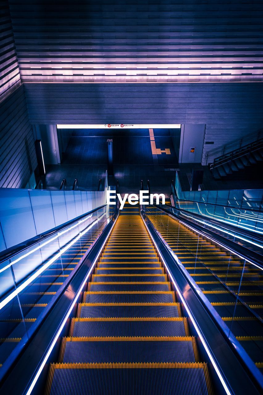 architecture, staircase, steps and staircases, illuminated, escalator, railing, indoors, modern, transportation, technology, lighting equipment, convenience, built structure, futuristic, arts culture and entertainment, night, subway station, city, no people, connection, moving walkway