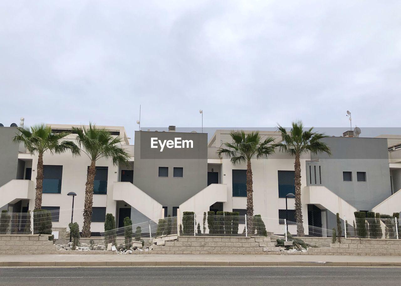 EXTERIOR OF MODERN BUILDINGS IN TOWN AGAINST SKY