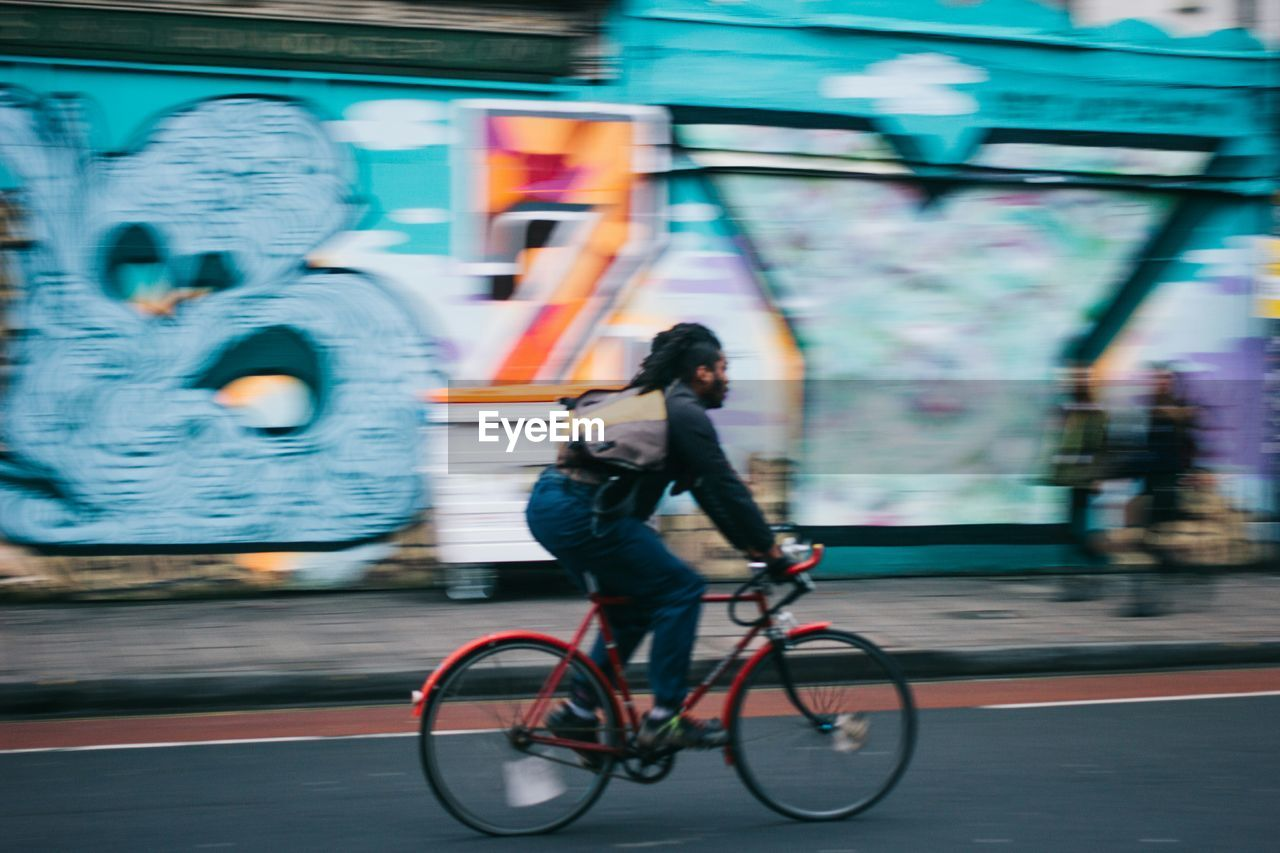 Full length of man riding bicycle on city street